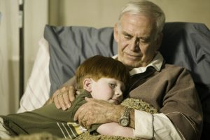 Grandson (8-9) hugging grandfather on bed in retirement home, close-up