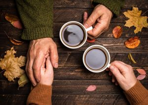 Old people holding hands. Senior people hand holding coffee cup.
